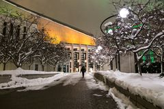 Woman walking at night in snowy alley towards the Place-des-Arts in the downtown sector, Montreal, Quebec stock photos