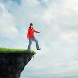 Woman walking off cliff Stock Images