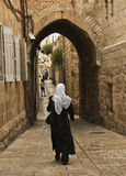 Woman Walking in the Old City, Jerusalem Israel. A woman in a long black coat  and black pants wearing a large white chiffon flowing scarf is walking down a Royalty Free Stock Photography