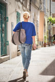 Woman walking on old cobbled street. Royalty Free Stock Images
