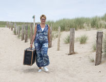 Woman walking with old suitcase on the beach Stock Photos