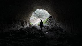 Woman walking out from the ancient underpass in Nysa, Sultanhisar, Turkey. Light at the end of tunnel. 4k. Silhouette of a woman walking out from the ancient stock footage