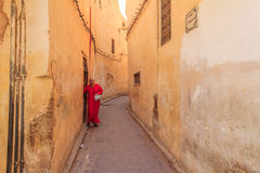 Woman walking out into a narrow street in the medina Royalty Free Stock Photo