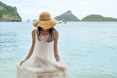 Woman walking out of the water in white dress. No face shown Stock Photos