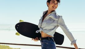 Woman walking outdoor on summer day with a skateboard. Woman walking outdoor on summer day with a skate board. Smiling caucasian female on a summer holiday Stock Photo