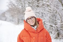 Woman walking outdoor in winter. Close-up portrait shot a happy woman wearing hat and warm coat while standing outdoor and enjoy winter weather Royalty Free Stock Photography