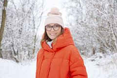Woman walking outdoor in winter. Close-up portrait shot a happy woman wearing hat and warm coat while standing outdoor and enjoy winter weather Stock Images