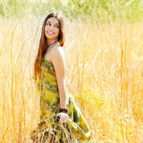 Woman walking outdoors in golden field. Asian indian woman walking outdoors in golden field with green long dress Stock Photography