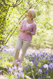 Woman walking outdoors holding flower smiling.  Royalty Free Stock Images