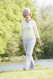 Woman walking outdoors at park by lake smiling Stock Image
