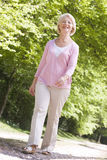 Woman walking outdoors smiling Stock Photography