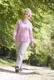 Woman walking outdoors smiling Stock Photos