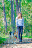 Woman walking outdoors smiling with dog Royalty Free Stock Photos