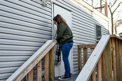 A woman locks her front door as she leaves home. royalty free stock image