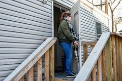 A woman walks out her front door to leave home. A woman walking outside the front door of her mobile home onto the front porch to turn and lock the door behind stock image