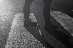 Woman walking over pedestrian zebra crossing Stock Image