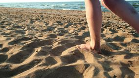 Woman walking over wet sand on beach. Female feet step on yellow sand from seashells. Happiness and freedom. Woman walking over wet sand on beach. Female feet stock video footage