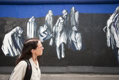 Woman walking by painting on Berlin Wall Stock Images