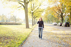 Woman Walking in Park and Calling by Phone Royalty Free Stock Photos