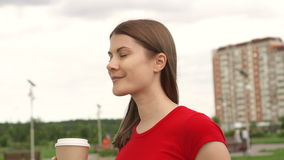 Woman walking in park drinking coffee, relaxing summer vacation, face smile. House on background stock footage