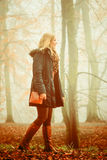 Woman walking in park in foggy day Stock Photo