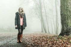 Woman walking in park in foggy day Royalty Free Stock Image