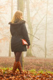 Woman walking in park in foggy day Stock Images