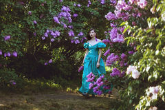 Woman is walking in the park of lilac. Stock Photos