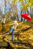 Woman walking in park with umbrella, strong wind Stock Photography