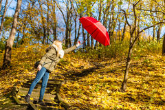 Woman walking in park with umbrella, strong wind Royalty Free Stock Images