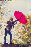 Woman walking in park with umbrella, strong wind Royalty Free Stock Photography