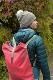 Woman Walking In Park. Young female with rucksack walking in the autumn park, verical outdoor shot Royalty Free Stock Photography