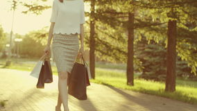 Woman walking in the park. Young woman with shopping bags walking in the park stock video