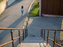 Woman walking past stairs and along path stock photo