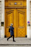 Woman Walking Past A Wooden Door