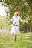 Woman walking on path smiling Royalty Free Stock Image