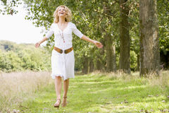 Woman walking on path smiling Royalty Free Stock Photos
