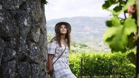 Woman walking on pathway between vineyard stock video