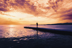 Woman walking on pier at sunset Royalty Free Stock Photo