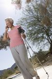 Woman With Walking Poles Using Cell Phone Stock Images
