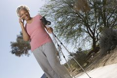 Woman With Walking Poles Using Cell Phone Royalty Free Stock Photography