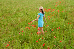 Woman walking in poppy field Stock Images
