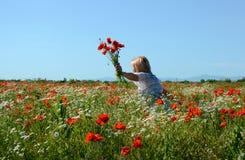 Woman walking on poppy field Royalty Free Stock Photo