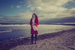 Woman walking on Portobello Beach, Edinburgh, Scotland. Brunette woman in red coat walking on waterfront of Portobello Beach, Edinburgh, Scotland on sunny day Stock Photography