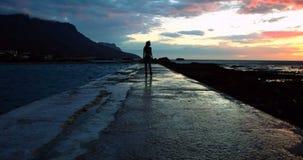 Woman walking on promenade at beach during dusk 4k. Silhouette of woman walking on promenade at beach during dusk 4k stock video