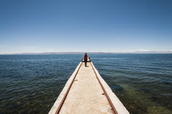 Woman walking in a quay above titicaca lake in an sunny day. Stock Photo