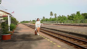 Woman walking on rail station platform with her bag stock footage