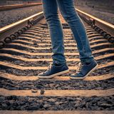 Woman walking on railroad. Female legs on the road Royalty Free Stock Image
