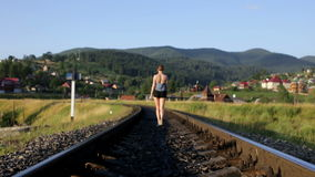 Woman walking on railroad in mountains stock footage
