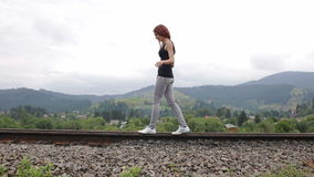 Woman walking on railroad in mountains stock video footage